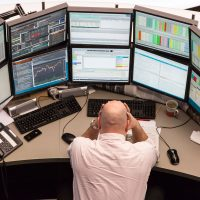 A financial trader reacts as he monitors data on computer screens at the Frankfurt Stock Exchange in Frankfurt, Germany, on Monday, March 9, 2015. With the European Central Bank buying its first government bonds this week to shore up the region's economy, options traders are showing little concern that the DAX Index might decline. Photographer: Martin Leissl/Bloomberg